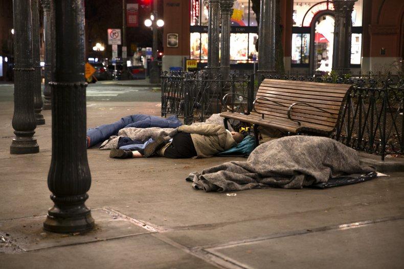 People sleep outside on a sidewalk on