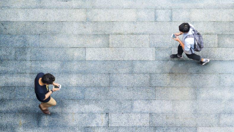 Two men walking looking at their phones
