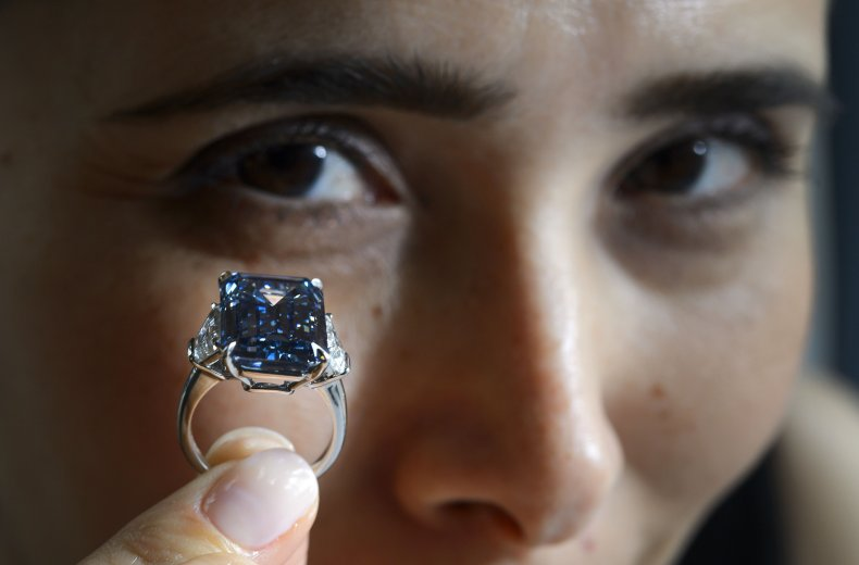"""A woman holds up the """"Oppenheimer Blue""""diamond."""