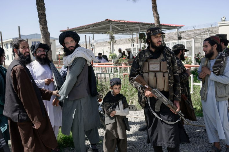An Afghan boy stands next to Taliban