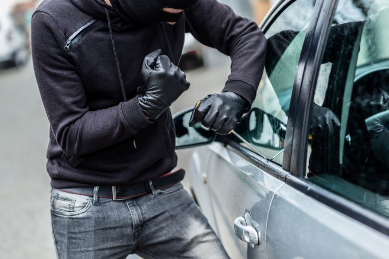 Man stealing car with mask on