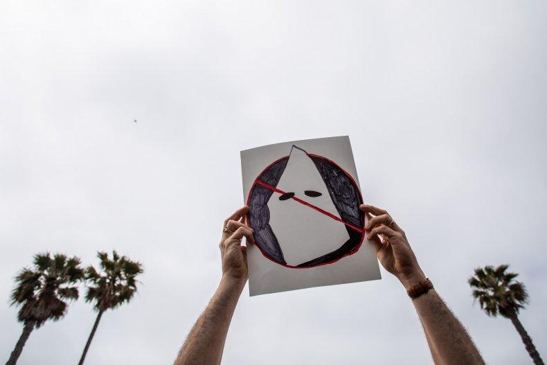 A man holds an anti-Ku Klux Klan