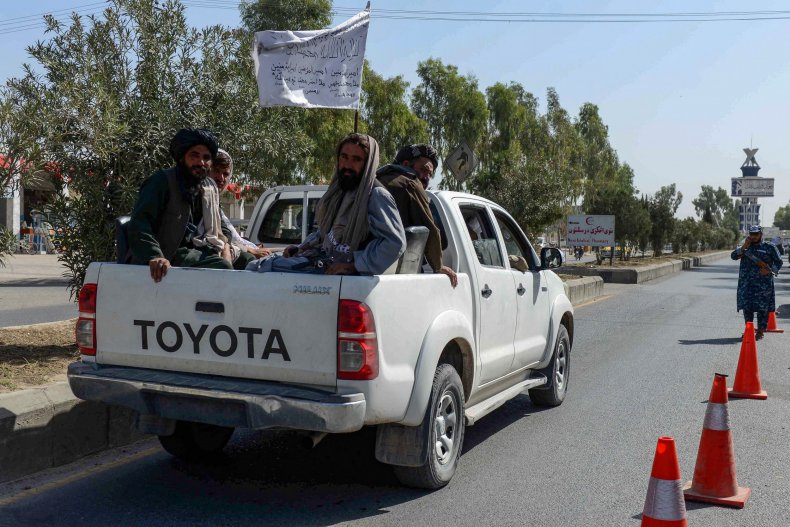 Taliban fighters sitting on a vehicle