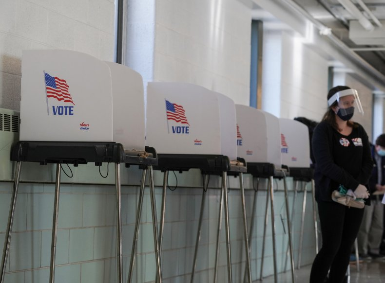 A poll worker stands by voting booths