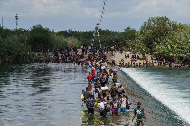 Migrants, many of them Haitian, cross the