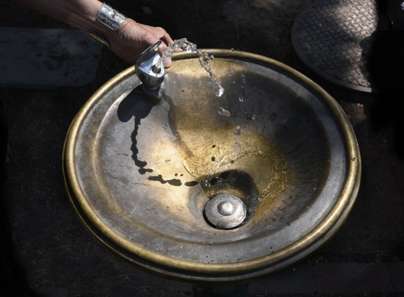 A woman uses a public drinking fountain