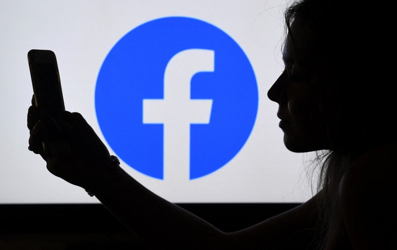 A person with phone against Facebook logo.