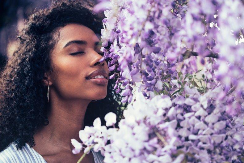 A woman smelling lavender flowers.