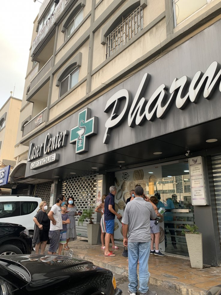 People are queuing in front a pharmacy