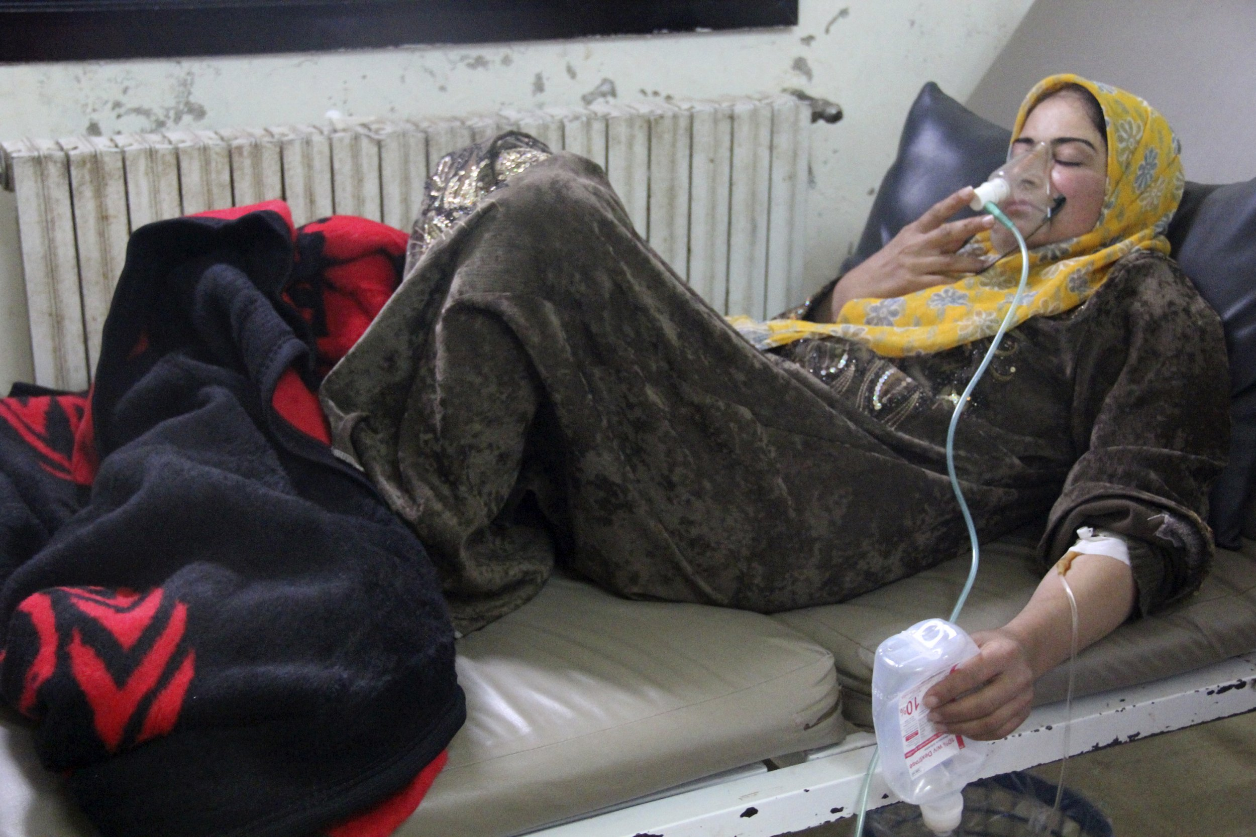 A woman, affected by what activists say was a gas attack, breathes through an oxygen mask inside a field hospital in Kfar Zeita village in the central ...