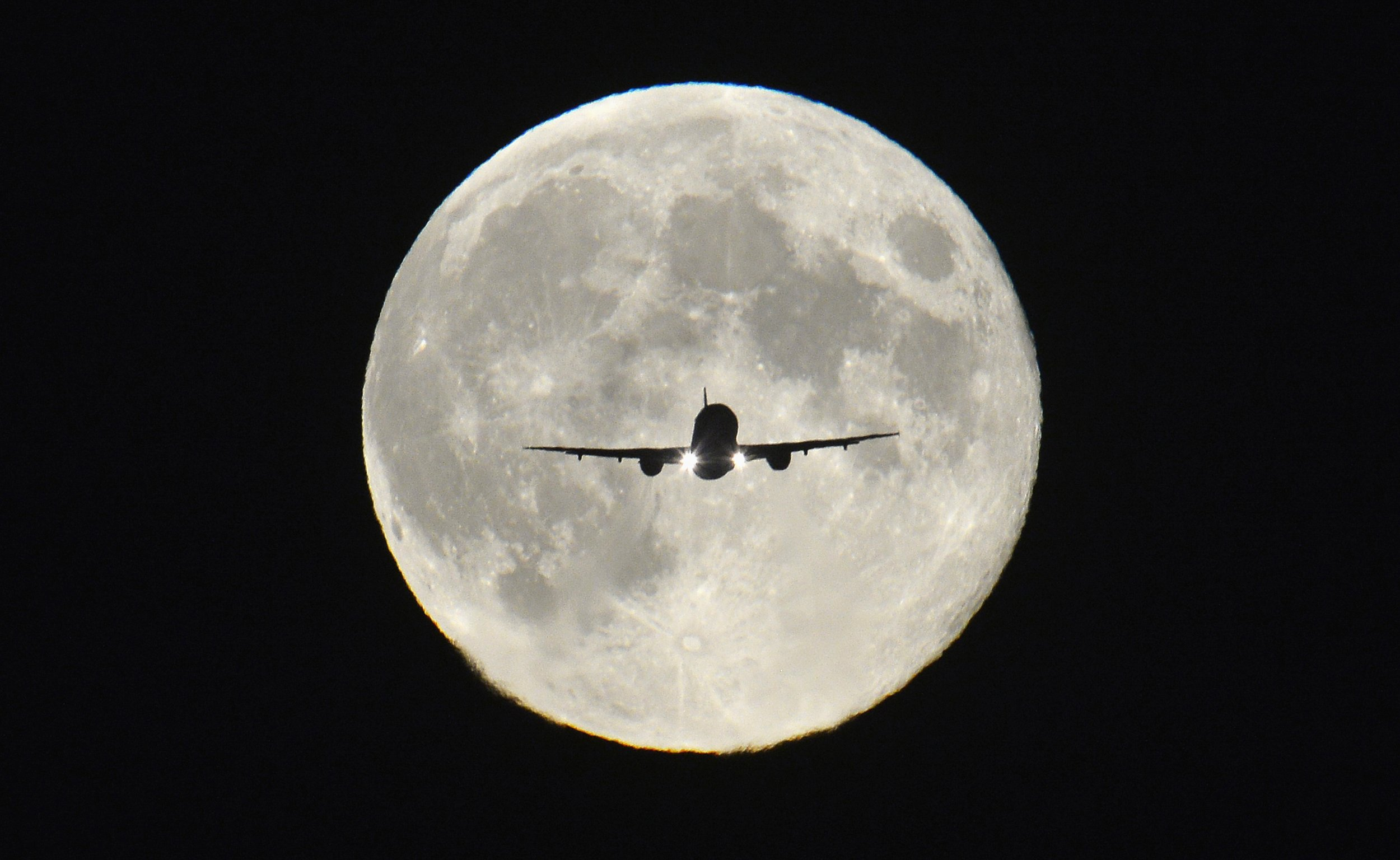 Plane flying in front of the moon