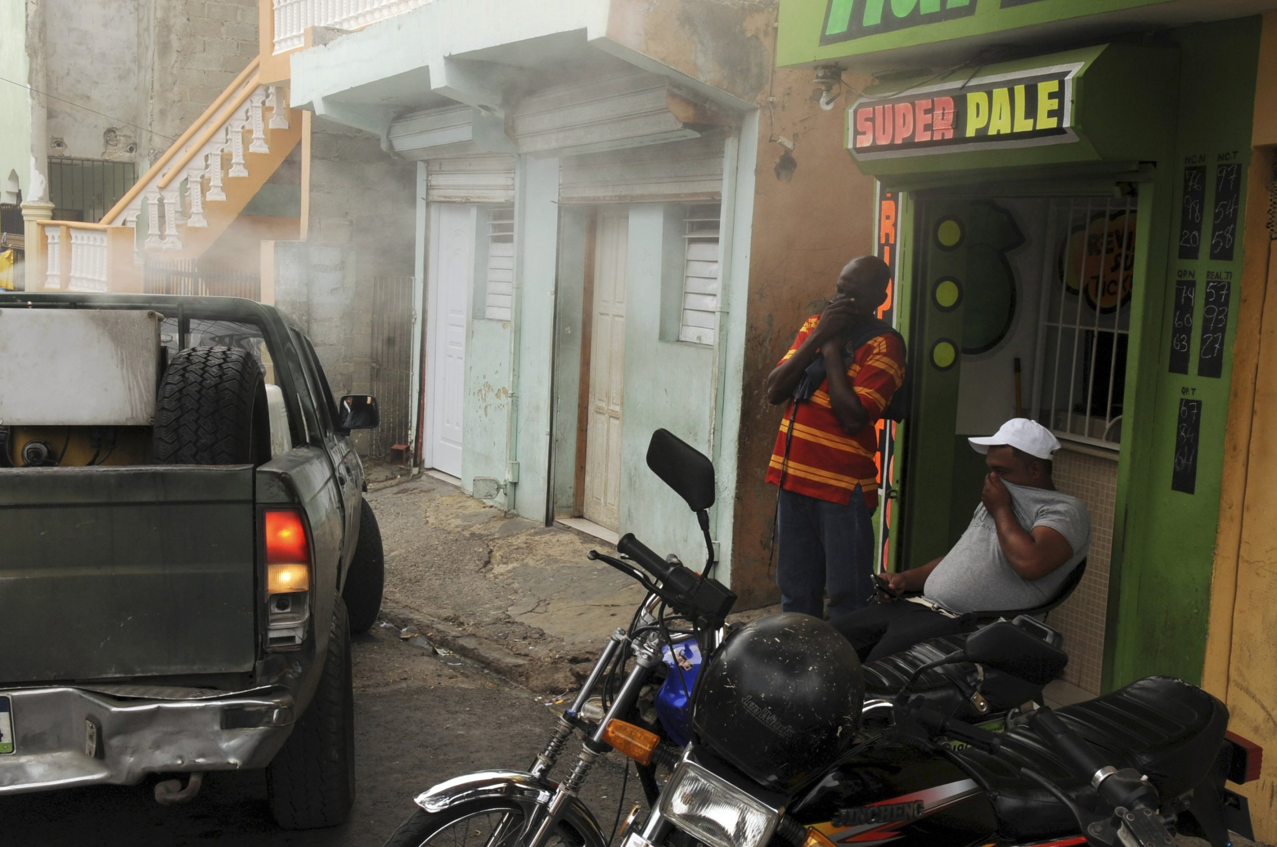 People cover their faces as a municipal truck is used to carry out fumigation against the mosquitoes that carry the Chikungunya virus in Santo Domingo.