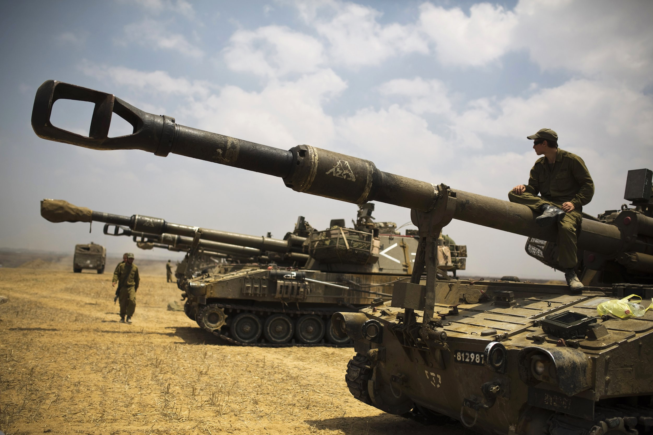 An Israeli soldier sits atop a mobile artillery unit in a staging area outside the Gaza Strip July 22, 2014.