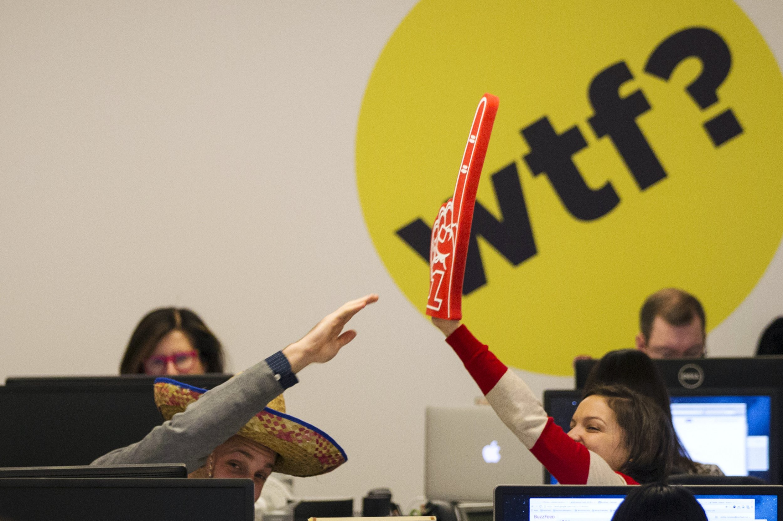 Buzzfeed employees trade high-fives while working at the company's headquarters in New York January 9, 2014.