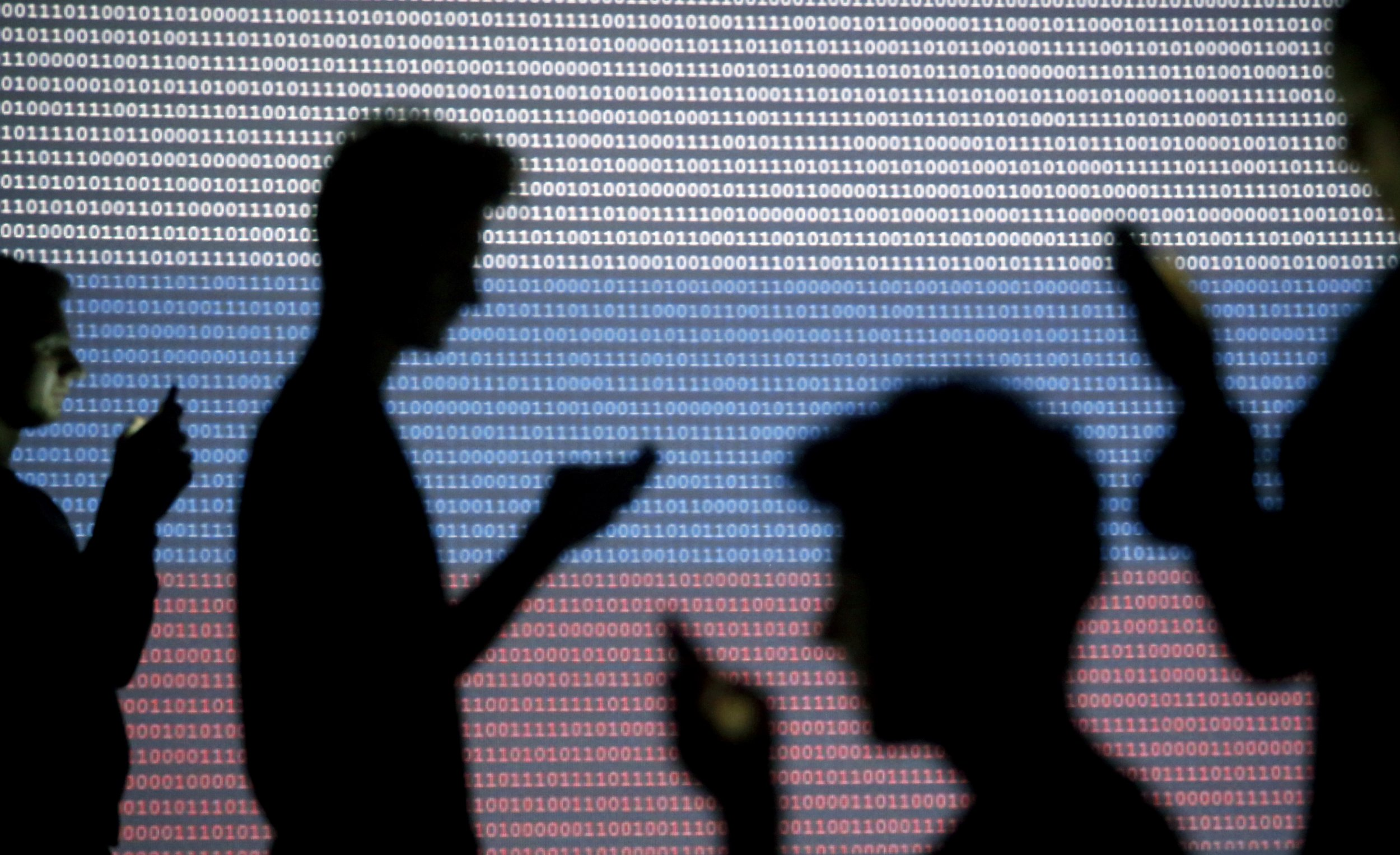 People are silhouetted as they pose with mobile devices in front of a screen projected with a binary code and a Russian national flag.