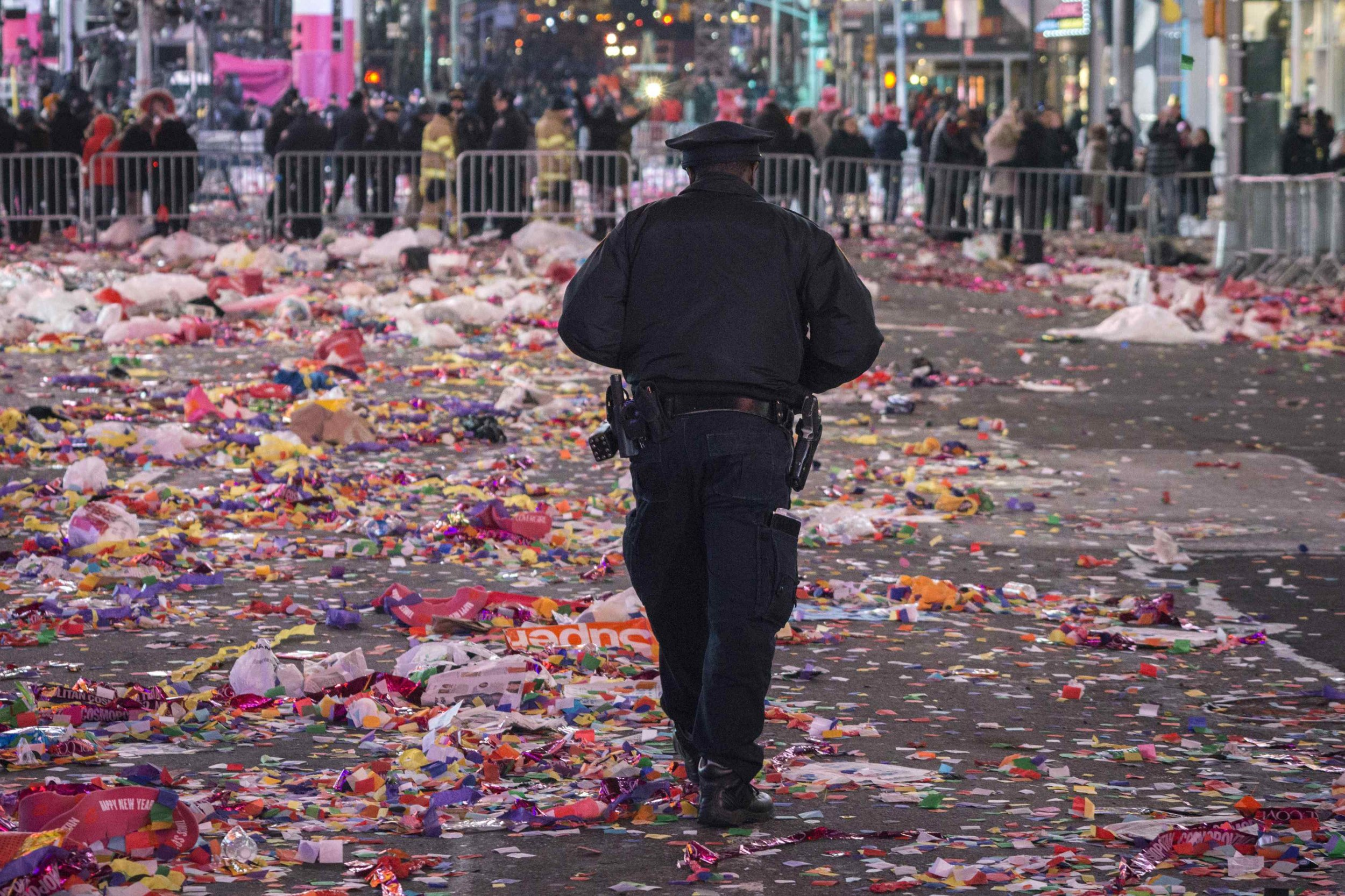 A cop walking through trashed Times Square on New Years, newsweek.com