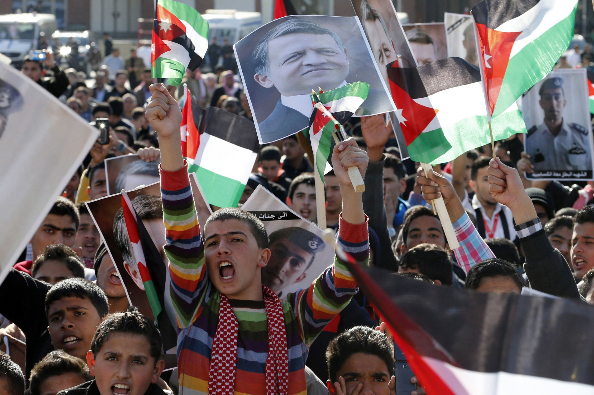 Protesters hold up pictures of Jordan's King Abdullah and pilot Muath al-Kasaesbeh