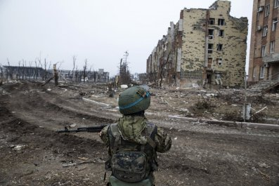 Pro-Russian separatist near a damaged building at Donetsk airport