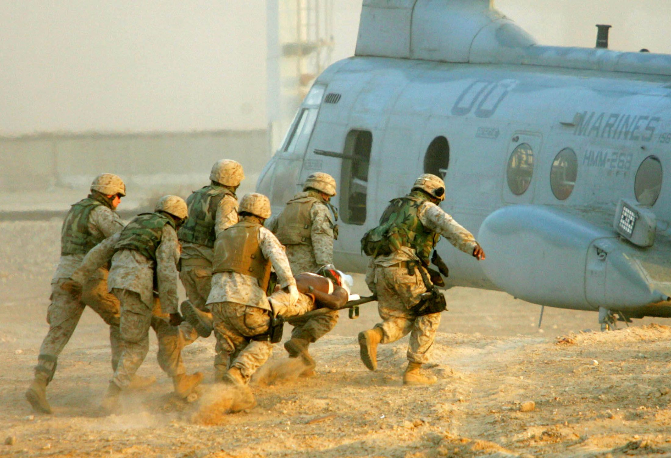 U.S. Marines carry an injured colleague to a helicopter near the city of Falluja, November 10, 2004. ELIANA APONTE/REUTERS