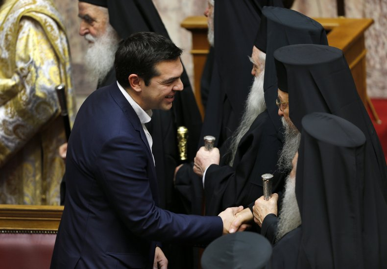Greek Prime Minister Alexis Tsipras greets Orthodox priests in the Greek parliament in Athens