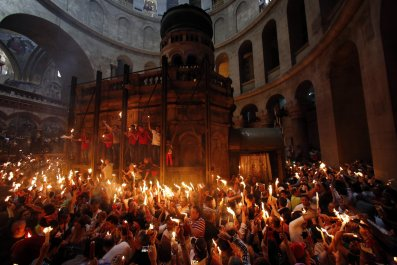 Worshippers hold candles as they take part in the Christian Orthodox Holy Fire ceremony in Jerusalem.