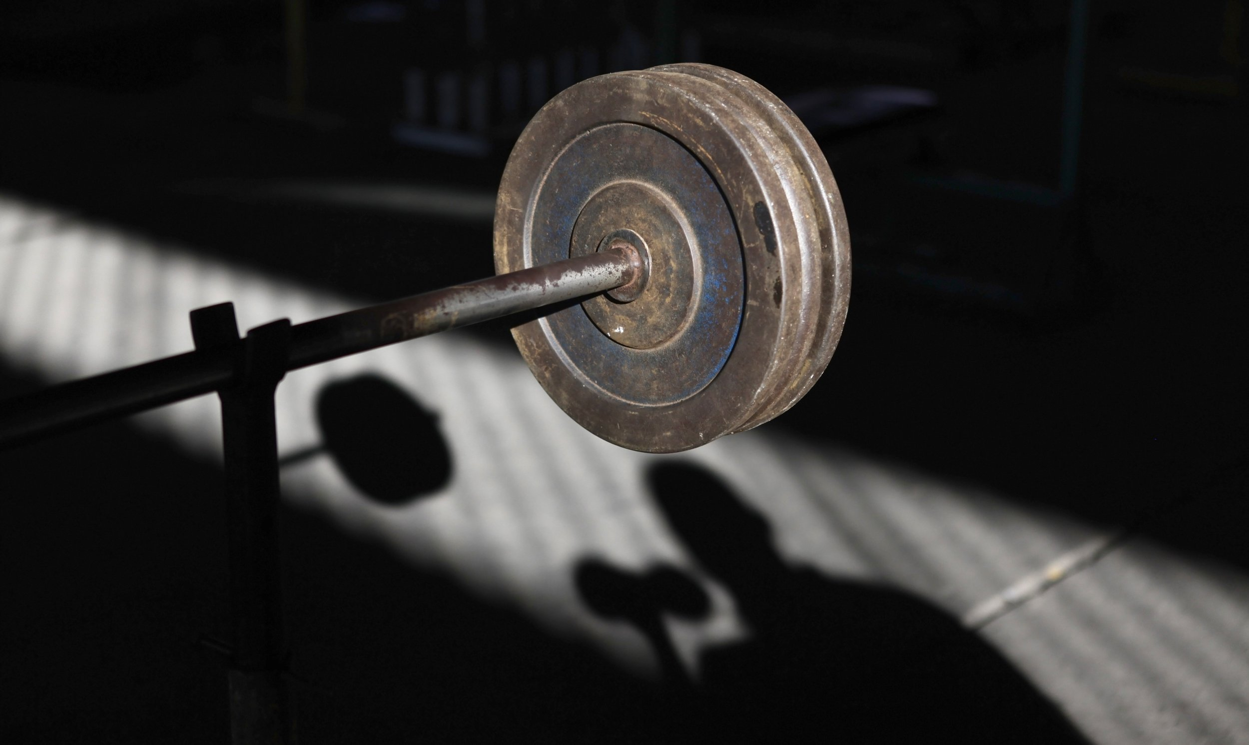 Weights are seen near the shadow of a man at a gym
