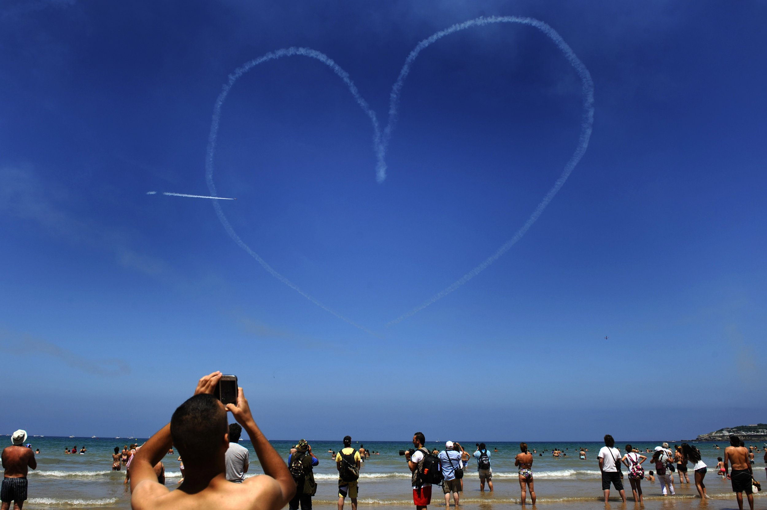 Beach goers watch a Spanish Air Force jet fly over a beach in Northern Spain