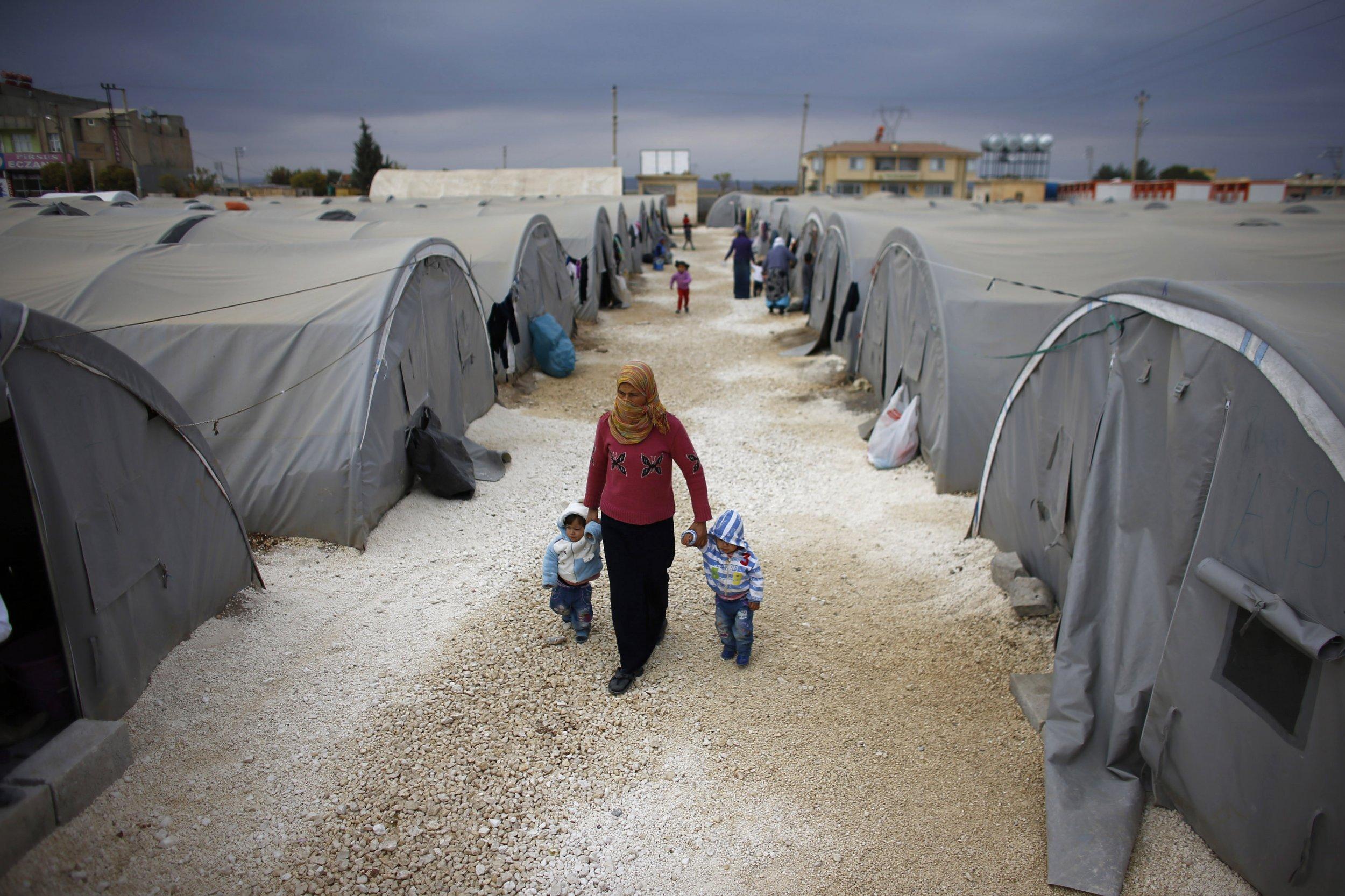A Kurdish refugee from Syria walks with her children at a refugee camp in Turkey