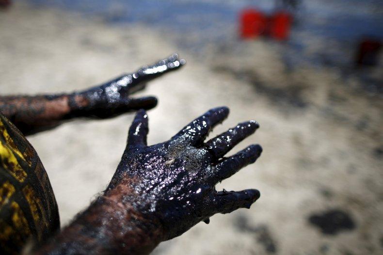 Volunteers clean crude oil off the beach
