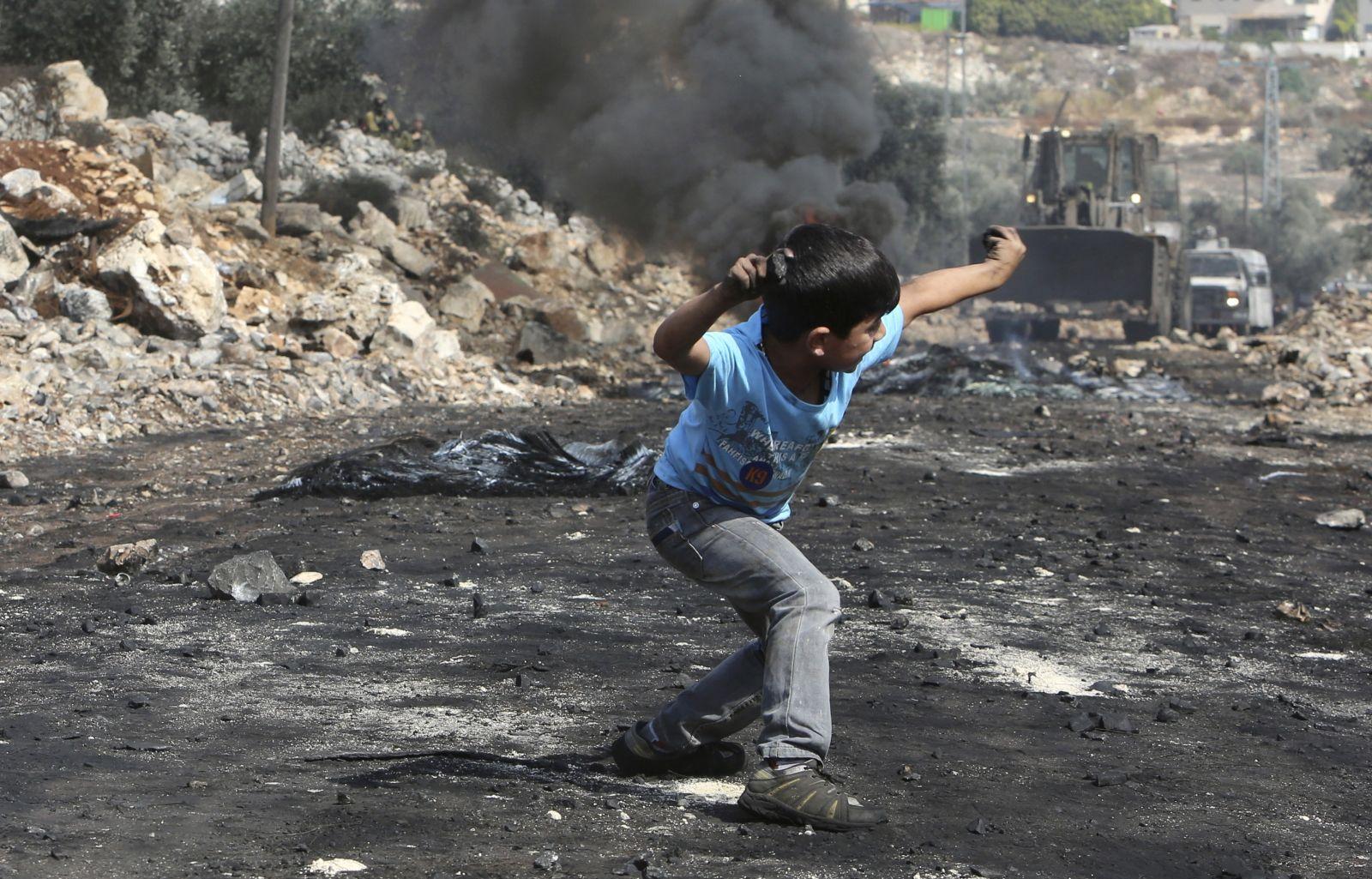 Palestinian boy throws stones