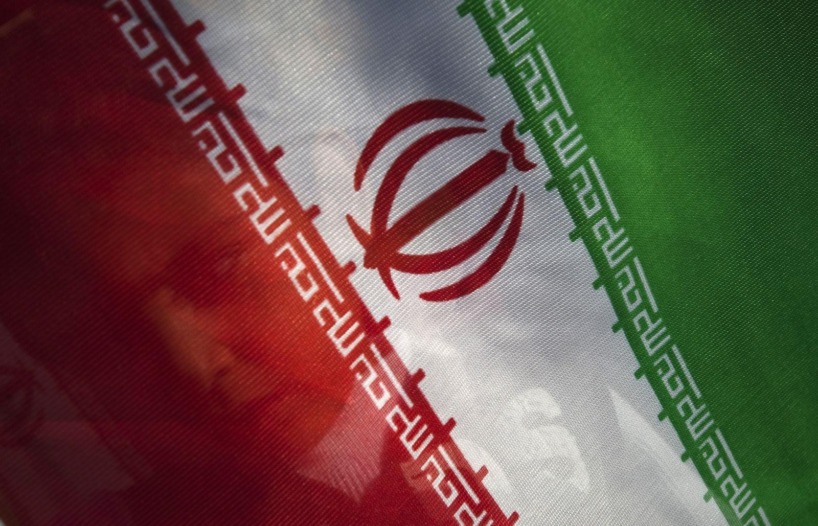 Young boy stands behind an iranian flag morteza nikoubazl reuters