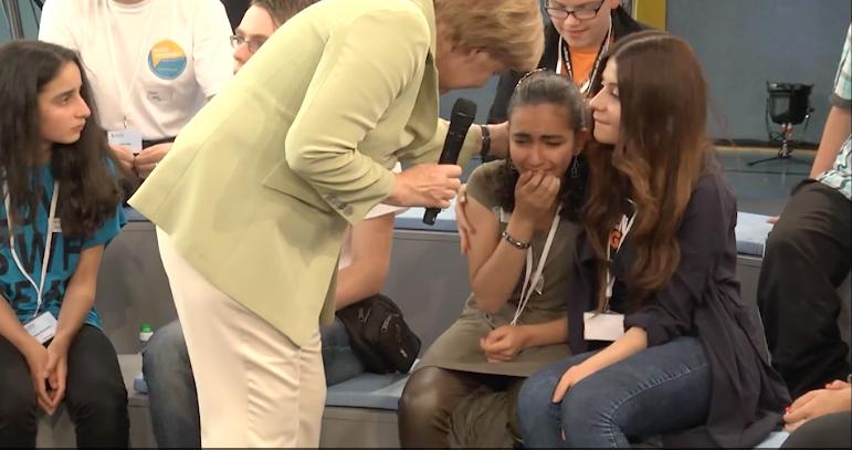 Angela Merkel comforts asylum seeker