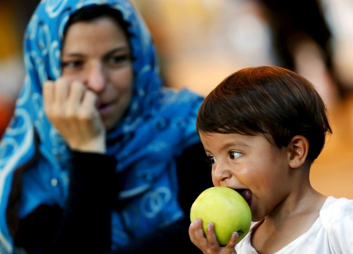 Child Refugee Eats An Apple