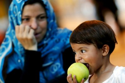 Child Refugee Eats An Apple