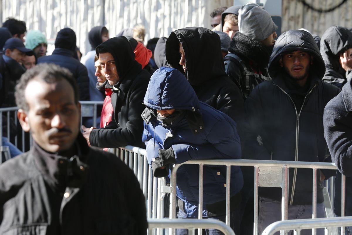 Migrants wait outside Berlin registration center