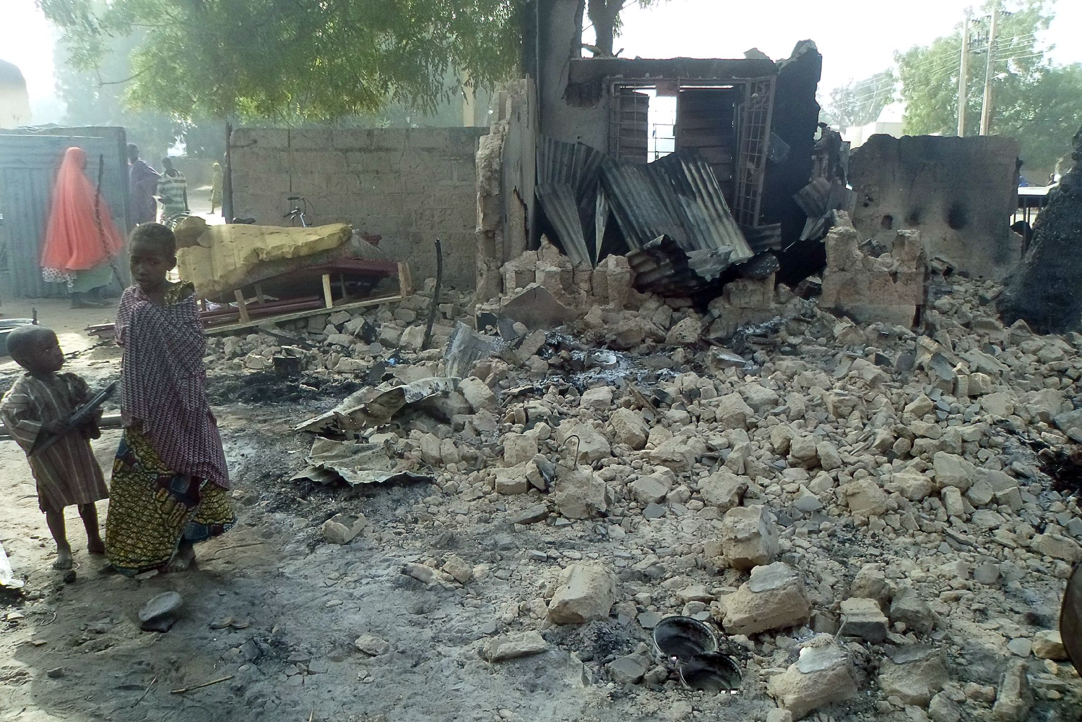 Children stand near rubble after Boko Haram attacks in Dalori, Nigeria.