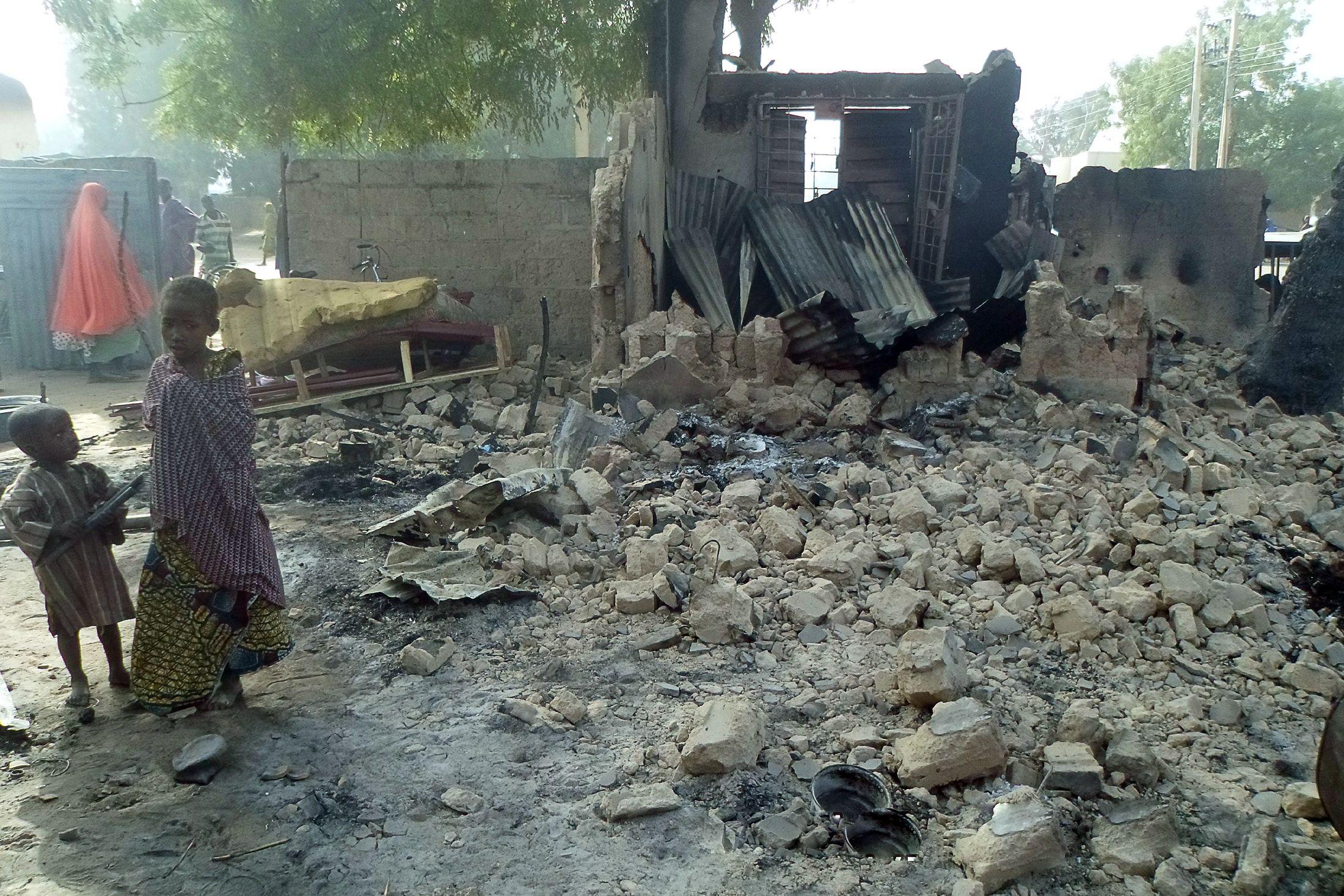 Children stand near rubble after Boko Haram attacks in Dalori, Nigeria.