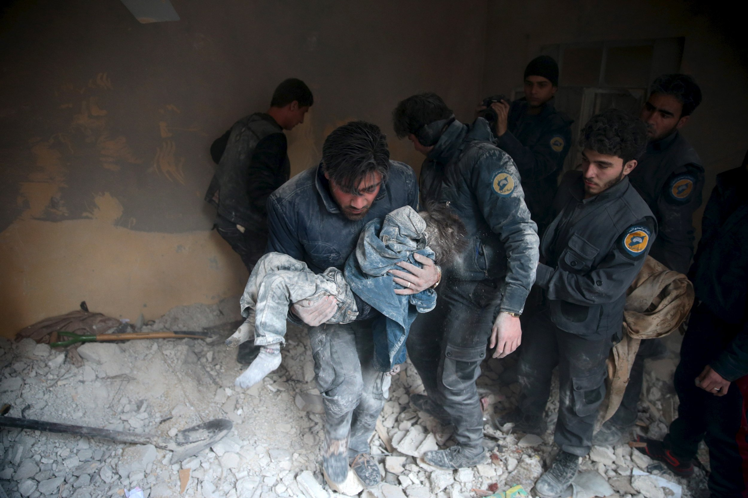 A man carries a child from debris in Damascus after what activists claim was a Russian airstrike.