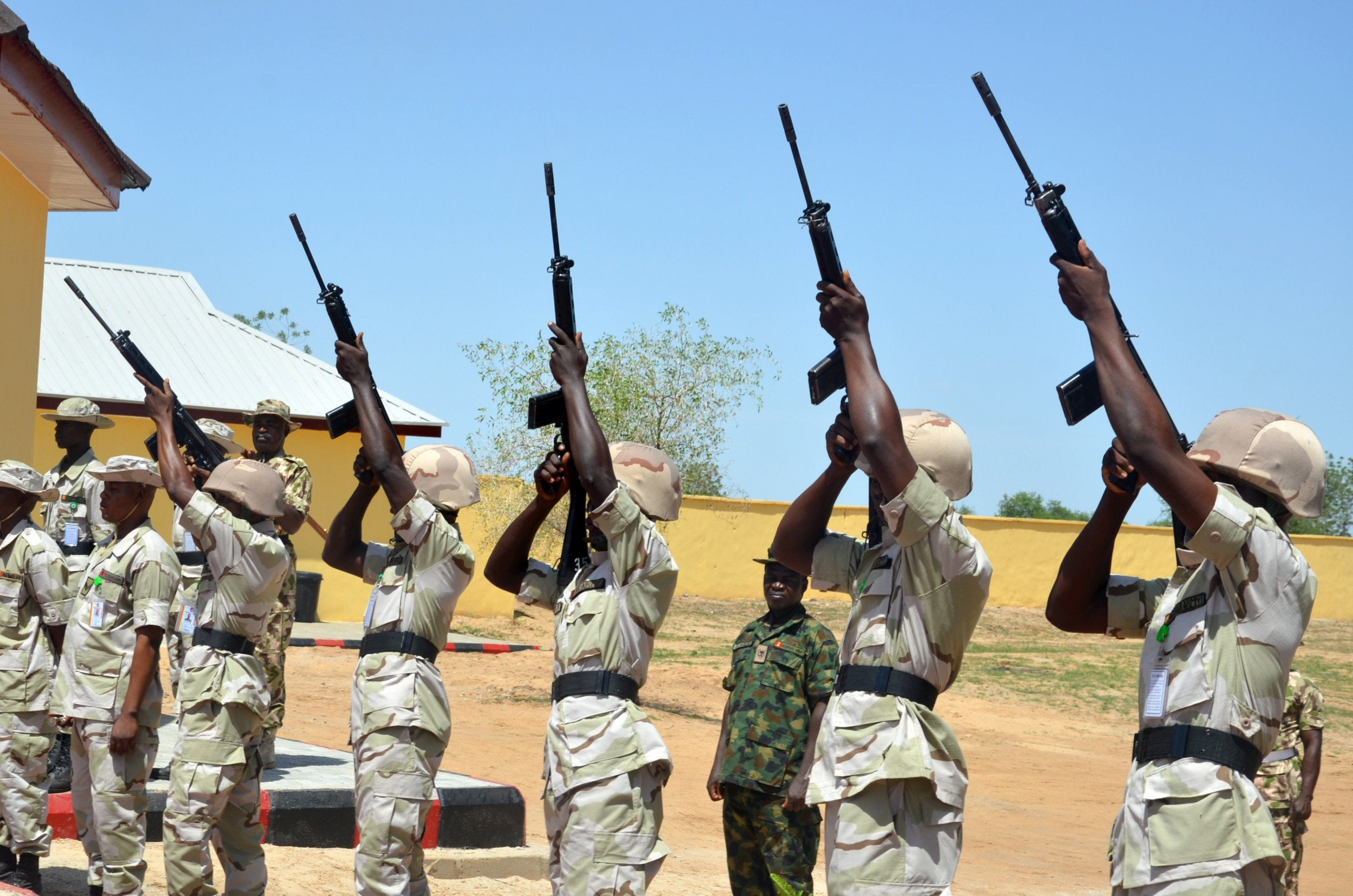 Nigerian soldiers shoot into the air to mark release of detainees cleared of being Boko Haram members.