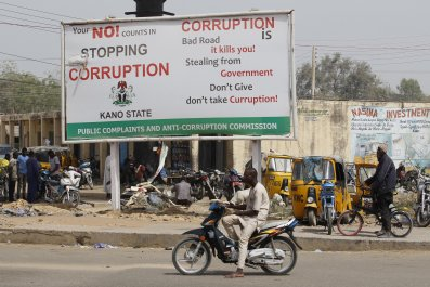 A motorcyclist sits near an anti-corruption sign in Kano, Nigeria.