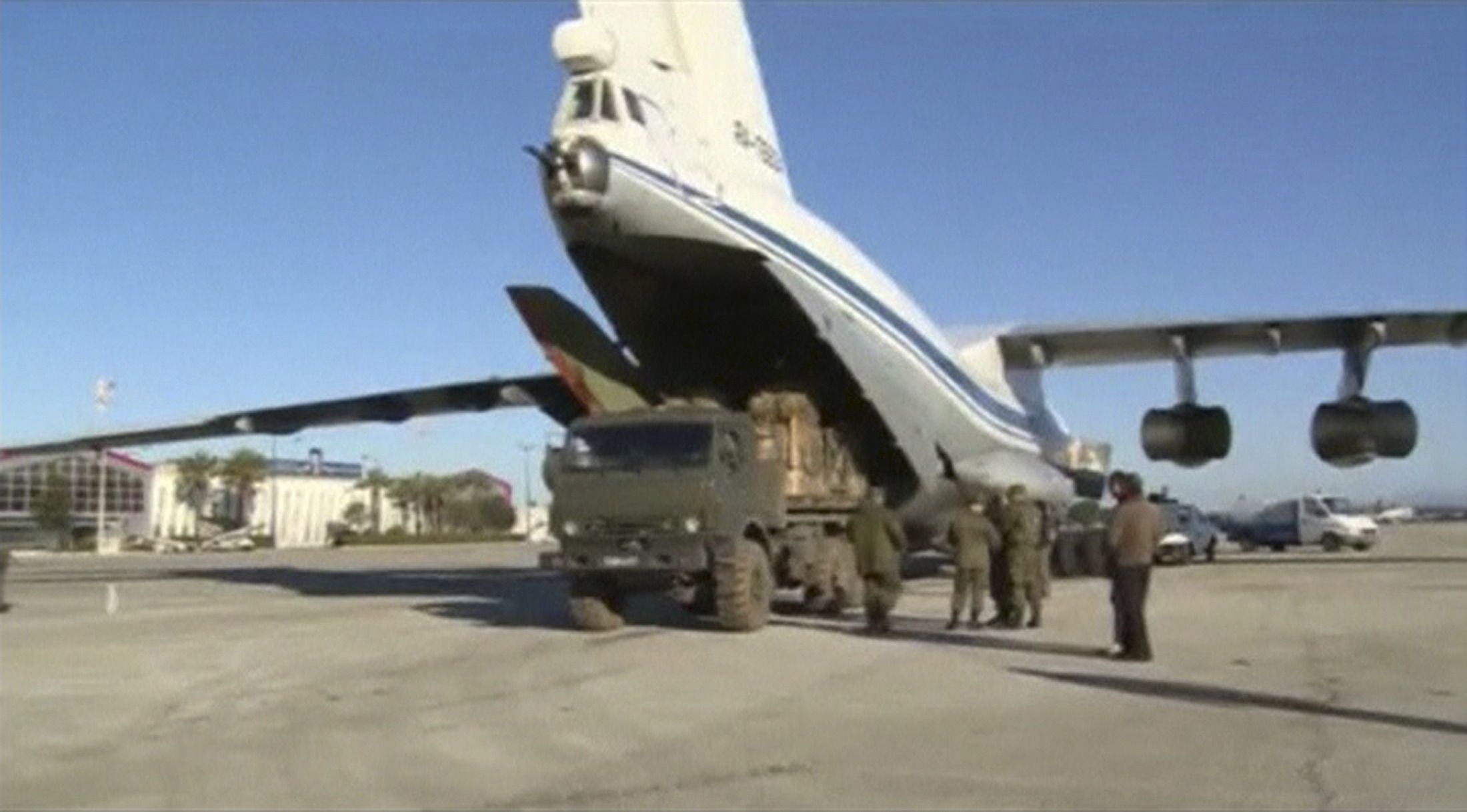 Russian cargo plane is being loaded at an airstrip