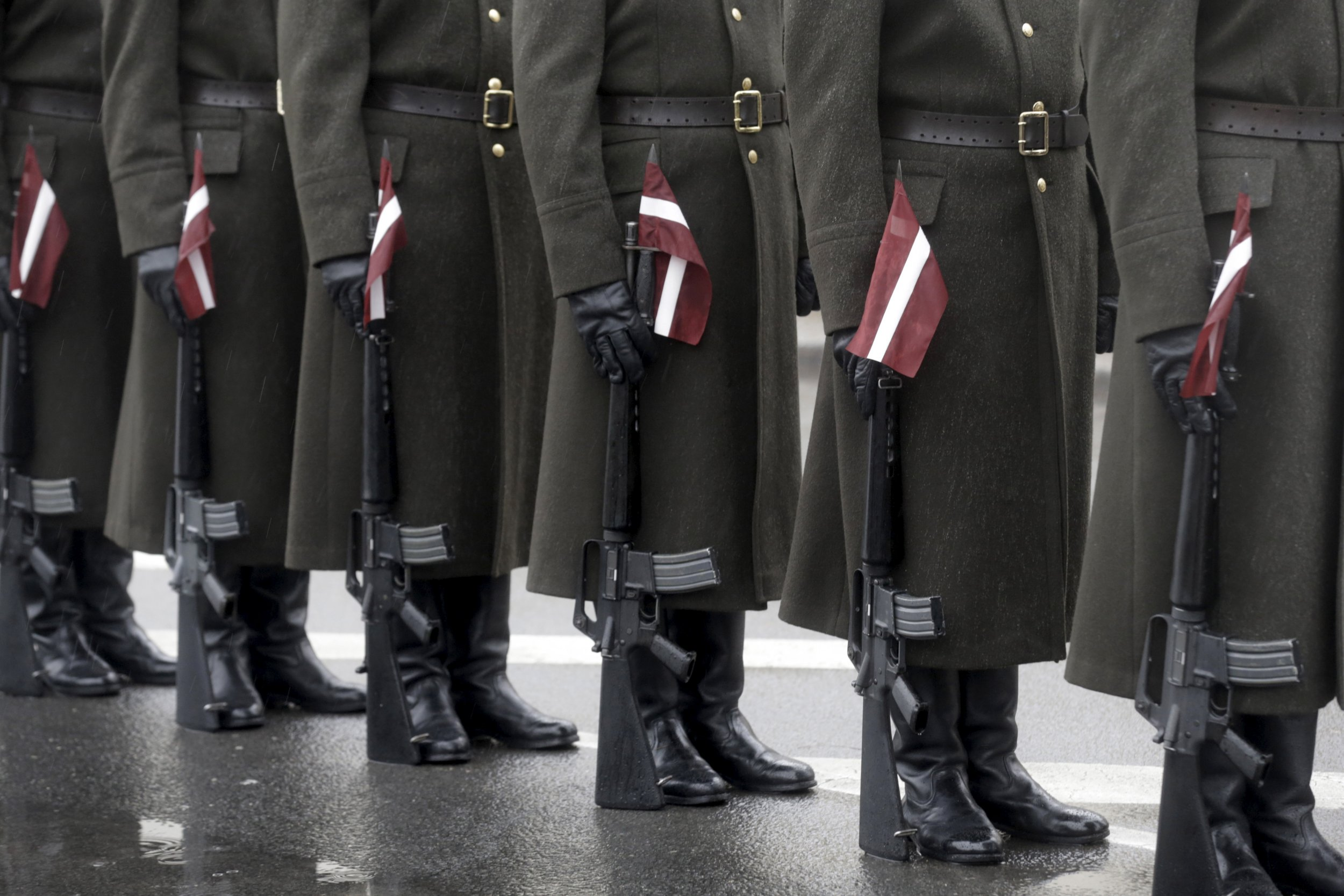 Latvian Soldiers stand to attention with flags at their side