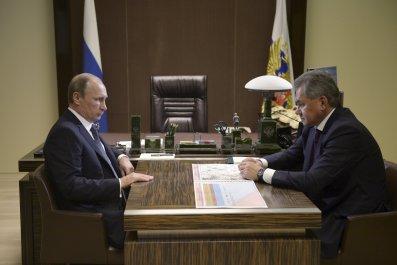 Putin sits opposite Shoigu at his desk