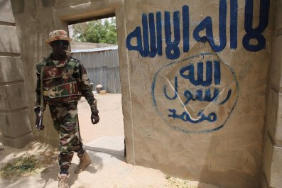 Nigerien soldier walks out of a house reportedly seized by Boko Haram in Damasak.