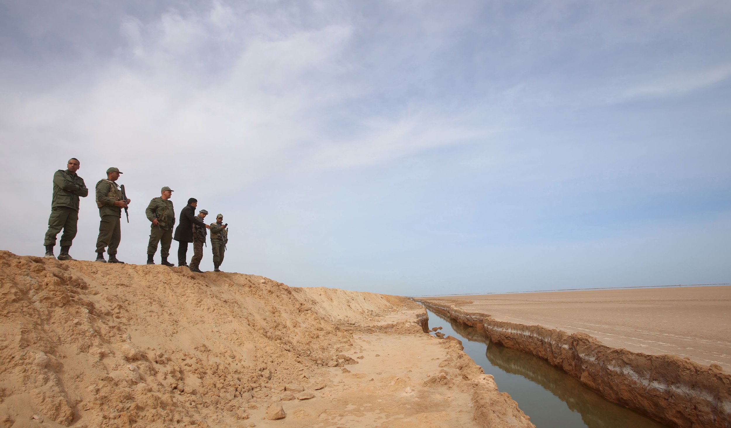 Tunisian soldiers look at the border barrier with Libya.