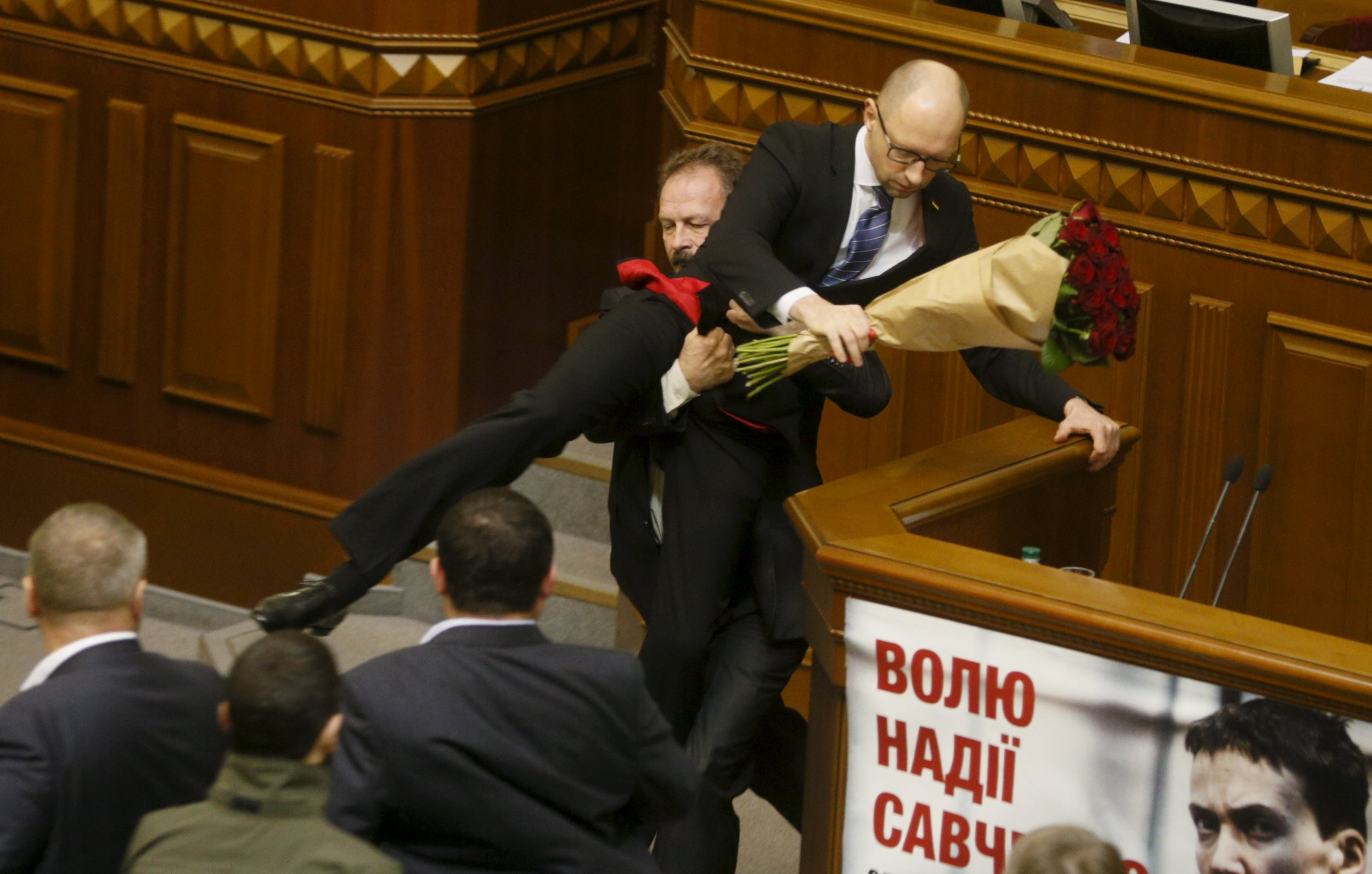 Ukraine PM Yatseniuk is pulled from the podium in parliament by MP
