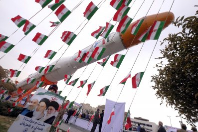 Iranian boy stands in front of missile surrounded by Iranian flags