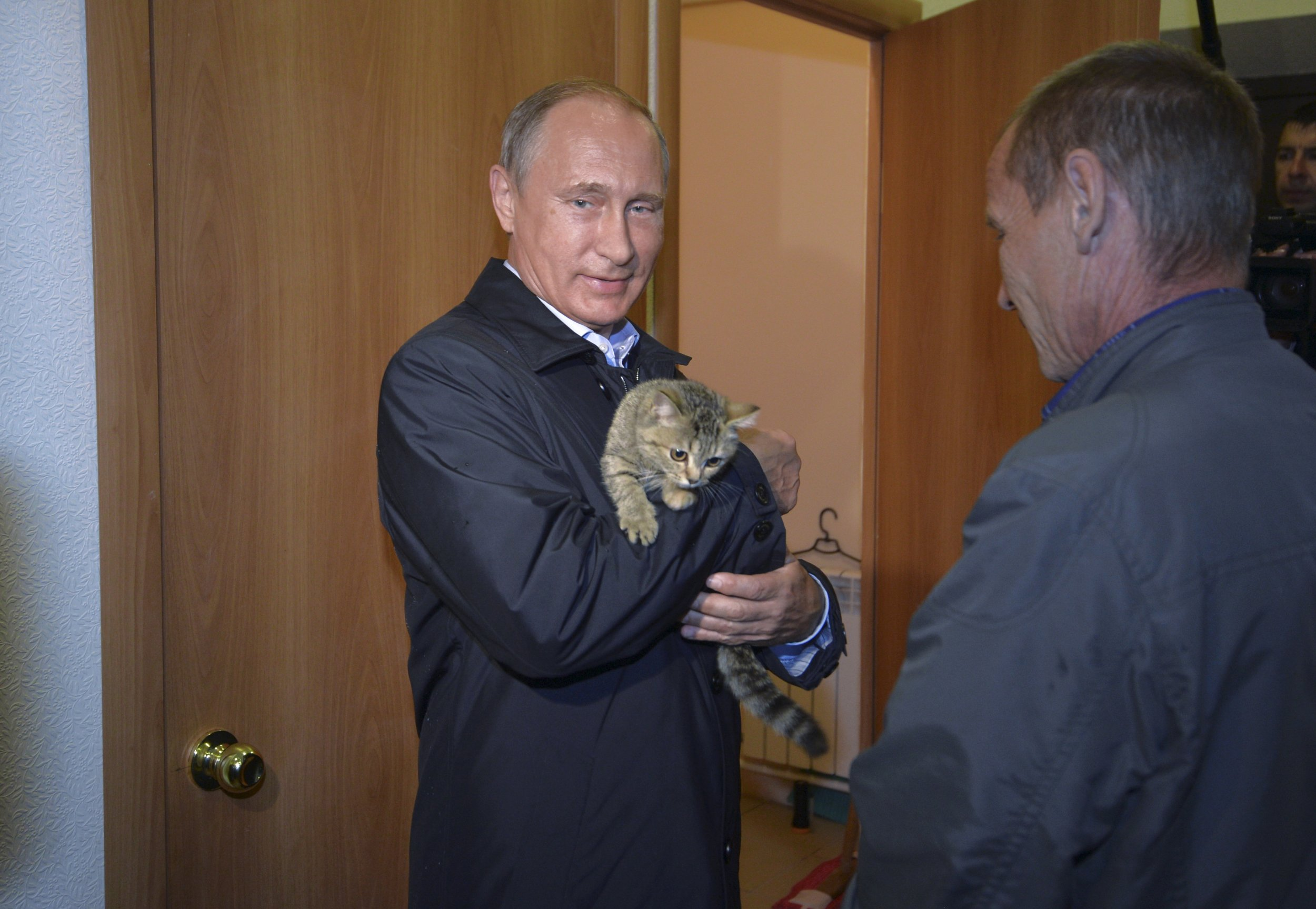 Putin smiles while holding a cat