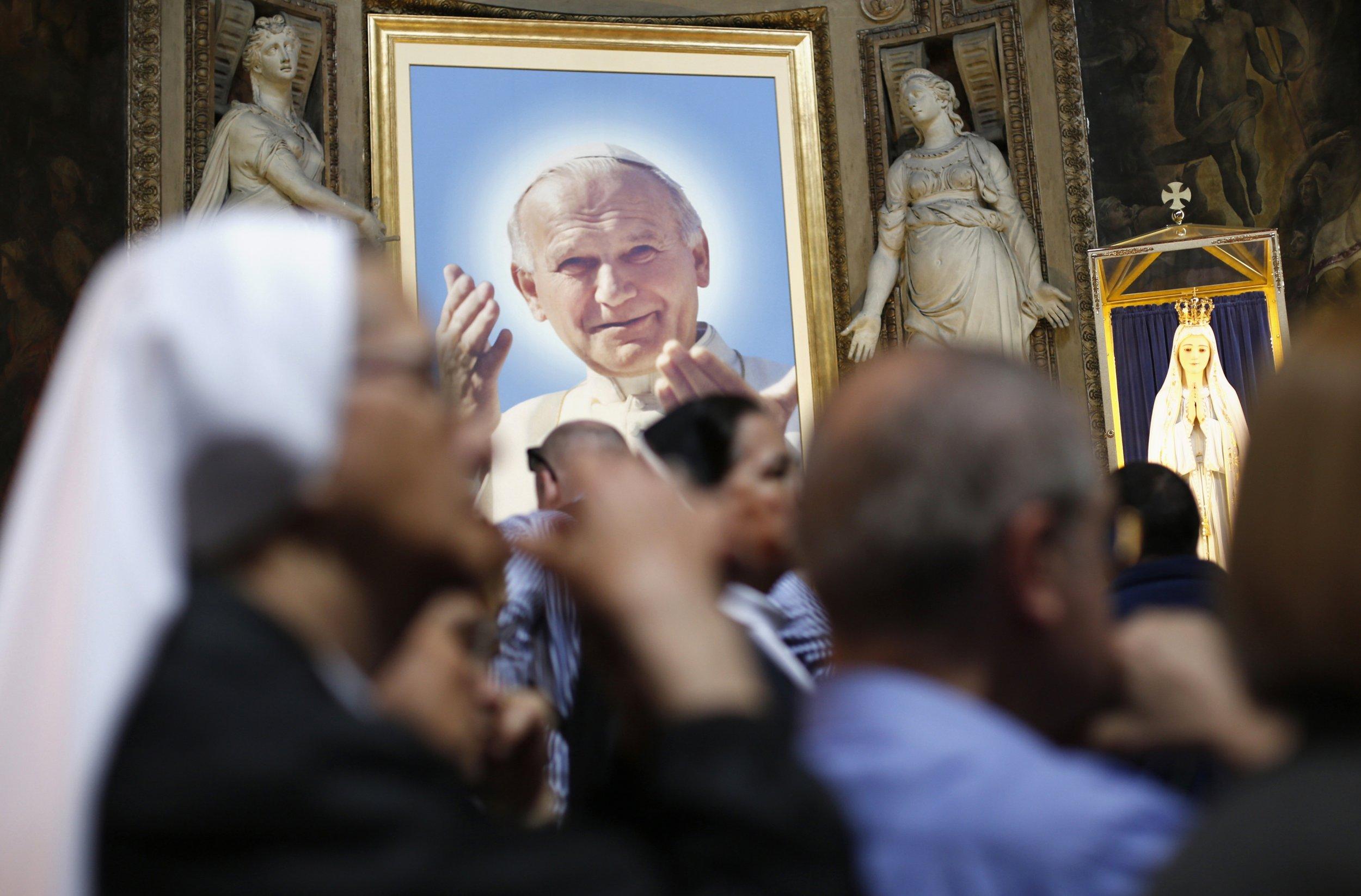 A nun prays near a portrait of Pope John Paul II.