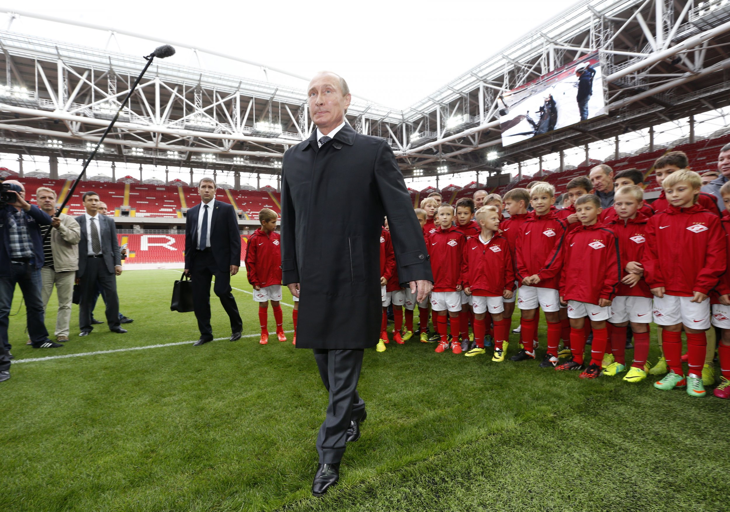 Putin stands in front of young soccer players in new stadium